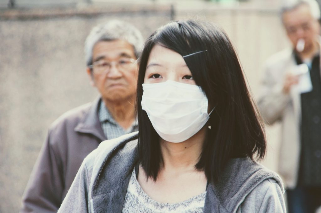 A woman wearing a respiratory mask over her nose and mouth