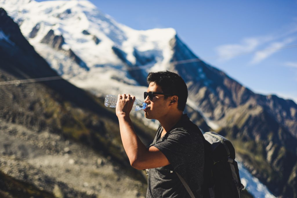 Man drinking water at the top of a mountain